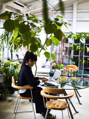 Artist Takahashi Kiroko works on the second floor of her Tokyo studio while surrounded by plants.