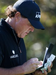 Phil Mickelson filling out his scorecard. Why do tournament golfers still need to do this?