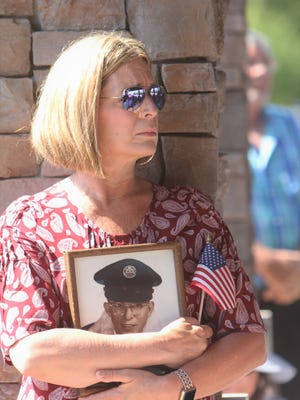 "Kelly Bobo holds a picture of her father, who died in November and is buried at M.J. ""Dolly"" Cooper Veterans Cemetery."