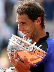 Spain's Rafael Nadal bites the cup after his victory over Switzerland's Stan Wawrinka in their final match of the French Open tennis tournament at the Roland Garros stadium, Sunday, June 11, 2017 in Paris. Nadal has won his record 10th French Open title, beating No. 3 Stan Wawrinka in straight sets (AP Photo/David Vincent)