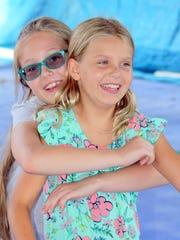 Jayden Kleine hugs her buddy Leah Tomblin as they radiate the spirit of Marco Y summer camps.