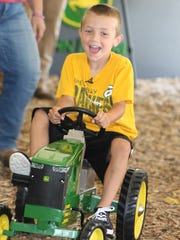 The smile says it all as Isaac Schneider tests out this John Deere pedal tractor.