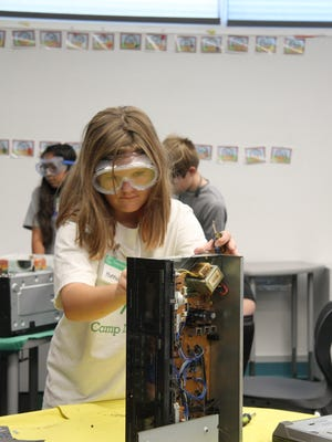 Fifth-grader Hannah Campbell breaks down electrical equipment at Camp Invention on Monday, July 17, 2017. Students in grades kindergarten through sixth will participate in activities such as developing alarm boxes and floor plans for stores during the five-day camp, July 17-21, 2017.