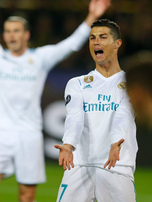 Real Madrid's Cristiano Ronaldo, right, and Real Madrid's Gareth Bale, rear, gesture during a Champions League Group H soccer match between Borussia Dortmund and Real Madrid at the BVB stadium in Dortmund, Germany, Tuesday, Sept. 26, 2017. (AP Photo/Michael Probst)