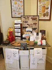 A table holds cheese accessories and other gift ideas inside Village Cheese Shop.