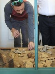 Barry Miller pores over artifacts fond beneath the