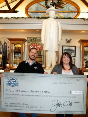 """from left: Brown-Forman's Mike Galvin recently presented a check in the amount of $11,919 to Karen Grimsley, Executive Director of the Armed Services YMCA of Fort Campbell, at the Jack Daniel's Visitor Center in Lynchburg, Tenn. Jack Daniel's representatives collected the funds at the 2017 Sturgis Motorcycle Rally in support of the """"Operation Ride Home"""" campaign that provides funding for junior enlisted service members and their families to travel from their base to homes around the country during the holidays."""