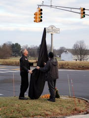 "Mark Henderson (right), father of Ashley Henderson-Huff, and Tom D'Alessio of Rolling Thunder, unveil the new street sign at the entrance to Montgomery Township High School, dubbing it ""1st Lt. Ashley Henderson-Huff Memorial Drive."" Ashley was a Montgomery High School 2000 graduate and a military police officer killed during duty in Iraq in 2006."