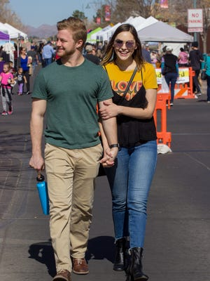 Chris Petro (left), 24, and Lindsey Livingston (right) 21, enjoy the warm weather Saturday afternoon as they roam the Downtown Farmers Market in Las Cruces, on Feb. 3, 2018