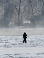 Unidentified man risks his life on the river ice at