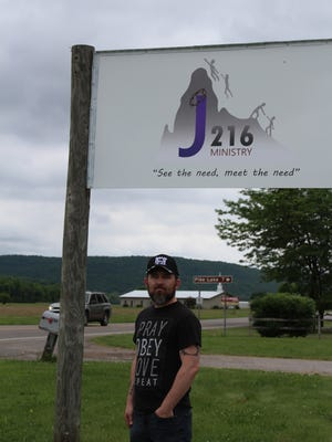Pastor Chas Cottrill poses in front of a sign for his church's ministry: J216 Ministry. The ministry has a rapidly growing food pantry that makes almost daily deliveries across multiple counties.