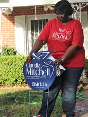 Claudia Mitchell, a candidate facing Robert Porterfield in a runoff election for the District 6 Board of Education Democratic nomination, fixes a fallen campaign sign will canvassing the Mobile Heights neighborhood on Tuesday, June 19.