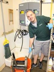 Garten Services custodial employee Jordan Clark uses a concentrated Green Seal certified cleaner that is diluted with water before use. Concentrated cleaners reduce waste and a preset dispenser ensures a consistent mix.