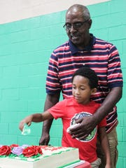 Keith Glover and his grandson, Benjamin Coddington, cut the cake at a family event in Collierville this month.