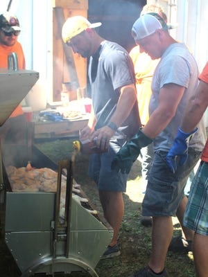 Hundreds of halves of chickens were prepared in large roasters by members of the Topinabee Fire Department, including Jason and Josh Vieau for their annual barbecue last Sunday. Photo by Kortny Hahn