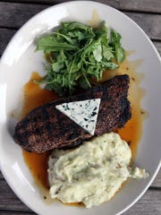 Coffee-crusted New York steak with baby wild arugula, blue affinee cheese, mashed Yukon gold potatoes and bourbon caramel at Salt Creek Grille in Rumson.