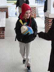 Cailfon resident Claire Janas, a member of the Class of 2023 at Gill St. Bernard's School in Peapack-Gladstone, brings in a frozen turkey for a past Take a Turkey to School Day. This year's event is Nov. 21.