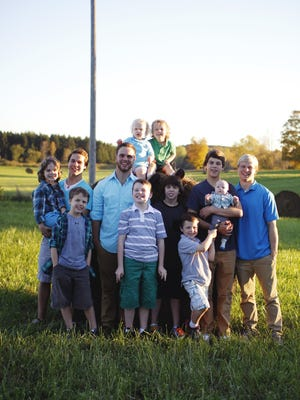Jay and Kateri Schwandt take a family photo with their 12 sons in 2013. They are, from left, Wesley, Drew, Calvin, Tyler, Luke, Vinny, Charlie, Tommy, Gabe, Brandon, Tucker and Zach. A new baby — possibly a girl — is due in May.