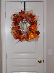 This rectangular lit wreath welcomes autumn with festive flair.
