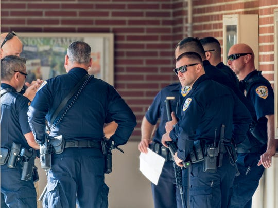 Visalia Police officers gather at Visalia Evangelical Free Church after looking for a man with a gun near Giddings and Main Street on Monday, March 12, 2018. Redwood High School was locked down for more than an hour but no person or gun was found in the area.