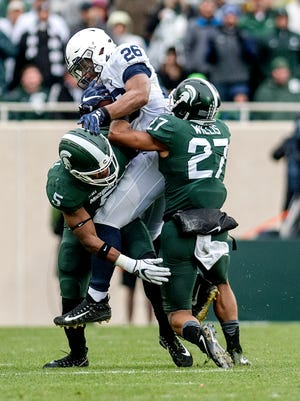 Michigan State's Andrew Dowell, left, and Khari Willis, right, tackle Penn State's Saquon Barkley during the first quarter on Saturday, November 4, 2017, at Spartan Stadium in East Lansing.