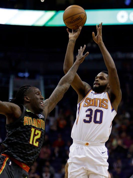 Phoenix Suns guard Troy Daniels (30) shoots over Atlanta Hawks forward Taurean Prince during the second half of an NBA basketball game Tuesday, Jan. 2, 2018, in Phoenix. The Suns defeated the Hawks 104-103. (AP Photo/Rick Scuteri)