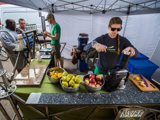 Steph Steeves, right, juices vegetables and fruit for