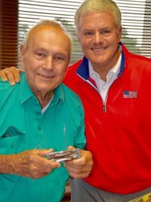 Scott Durham of Haddonfield presents golfer Arnold Palmer with an engraved knife tool for his  Coast Guard service in the 1950s
