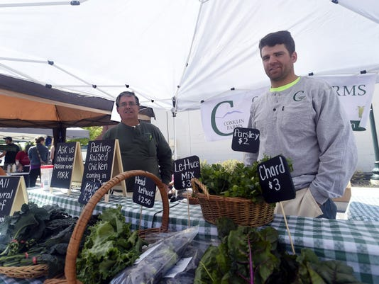 Joseph Conklin, left, and his son Joe sell vegetables and at the North Square Farmer Market, which opened in Downtown Chambersburg on Saturday,.