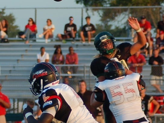 Viera defensive lineman Sebastian Noel tries to block a pass from New Smyrna Beach quarterback Marcus Johnson in the 2012 spring game.