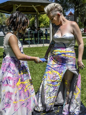 """Lilythe Knier, 10, left, adds some extra blue paint to her mom, Allison's, dress Saturday as the pair participate in the Family Crisis Services' """"Trash the Dress"""" event Saturday in A. Harold Long Park."""
