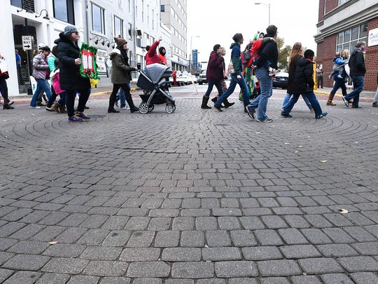 Participants in the Children's March on Evansville make their way through the intersection of third and Main Streets in downtown Evansville Sunday, November 12, 2017.