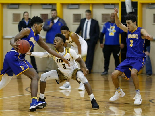 Irondequoit's Gerald Drumgoole dribbles as Greece Athena's Nigel Scantlebury tries to stop him while Irondequoit's Robert Diaz-Judson waits in the fourth quarter at Greece Athena High School.