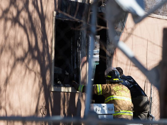 Doña Ana County Fire Fighters look around the burnt