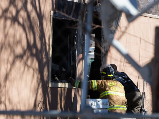Doña Ana County Fire Fighters look around the burnt mobile home for any hotspots that might remain after the fire was extinguished that was called in the morning,  Wednesday Feb. 7, 2018 at the Val Verde Park for Mobile Homes.