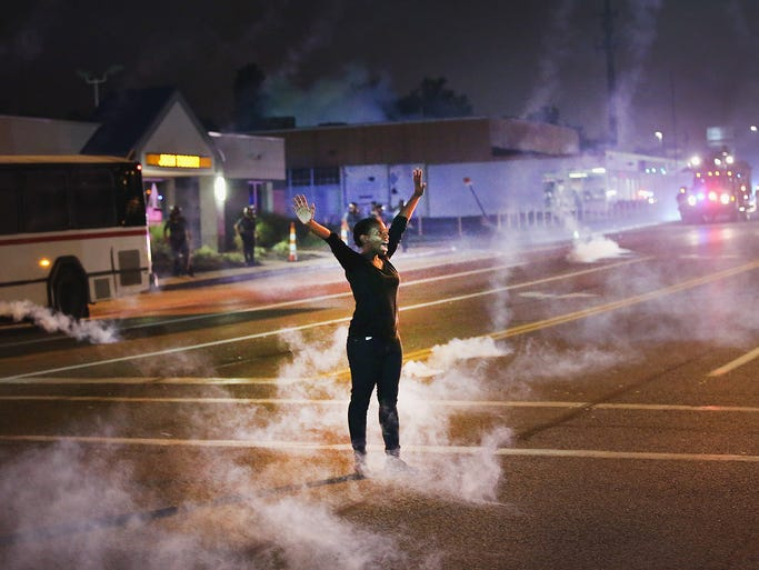 Tear gas canisters hit the pavement around a woman demonstrating on Aug. 17 against the killing of Michael Brown, 18, by a police officer in Ferguson, Mo. Despite the Brown family's continued call for peaceful demonstrations, violent protests have erupted nearly every night since his Aug. 9 shooting death.