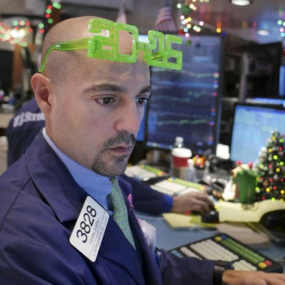 A trader wears glasses in the shape of 2015 while working