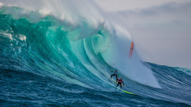 Josh Kerr, formerly of Australia, now San Deigo, California (pictured red) rides a wave with Carlos Burle of Brasil (white) during the final of the Todos Santos Challenge. Kerr won the event in monstorous 30-40-foot surf at Todos Santos off the coast of Baja, Mexico, on Sunday January 17, 2015.