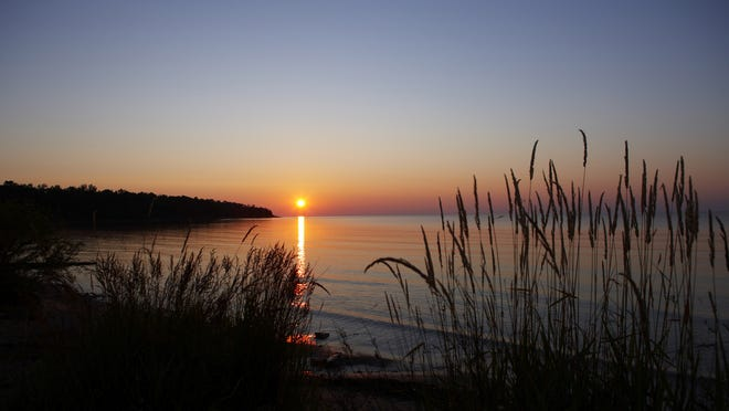 The sun rises over Newport State Park in Door County.