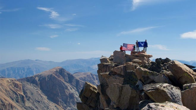 Hikers hold the United States and Air Force flag at the top of the highest mountain in Montana as part of the United States Air Force 50 Summits Challenge Aug. 4-6, at Granite Peak.
