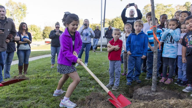 Stowe Elementary School student Sofia Puente shovels dirt in around an oak tree during the dedication of a memorial for fallen Des Moines police officers Carlos Puente-Morales, who is her father, and Susan Farrell on Oct. 7 at Stowe Elementary School.