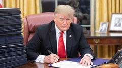 President Trump signing paperwork at his desk in the Oval Office.