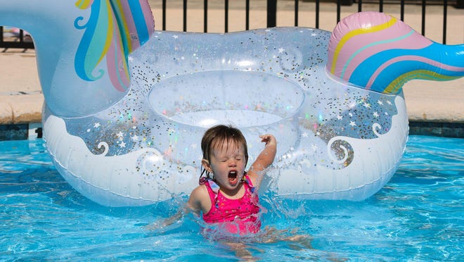 Gabriella Owen, 2, slides off the unicorn floaty and into the water at the Solomon Pool on Tuesday.
