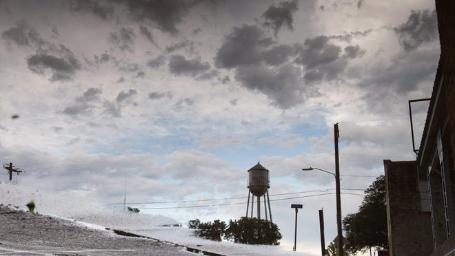 The water tower in Silver Lake is reflected in puddles after rain storms moved over the area last Friday.