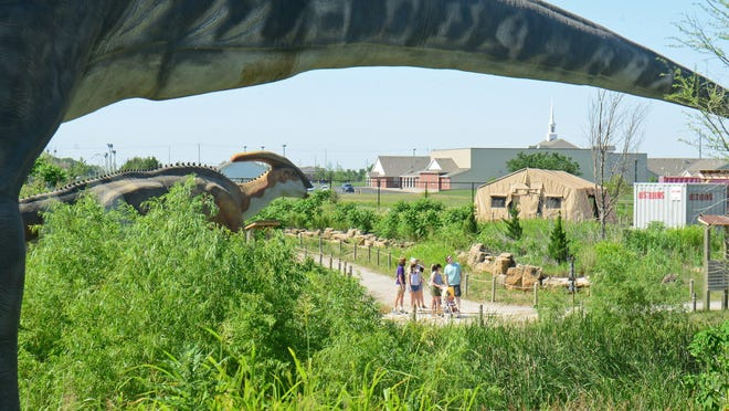 A family looks at the life size dinosaurs while walking on the 10-ares of trails at the Field Station: Dinosaurs park in Derby.