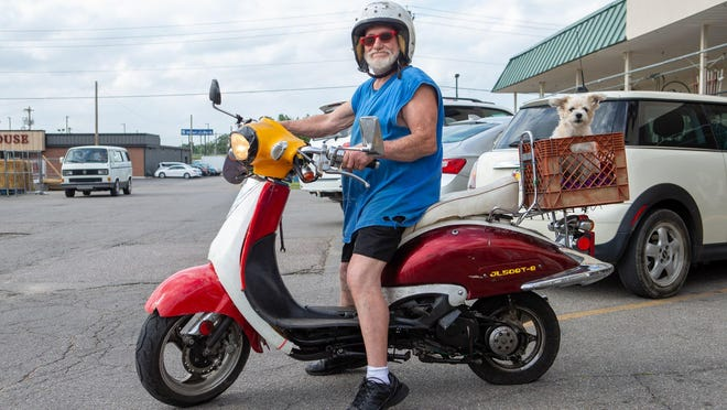 Willis Butchee rides with his dog Sweet Pea after a stop at Ace Hardware in Topeka on Monday.