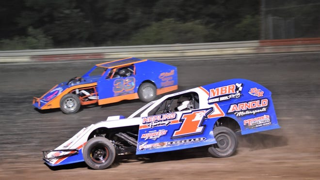 Kyle Moore works his way through lap traffic on his way to victory lane in the Bugs-R-Gone modified division on Thursday at the Hilltop Speedway.