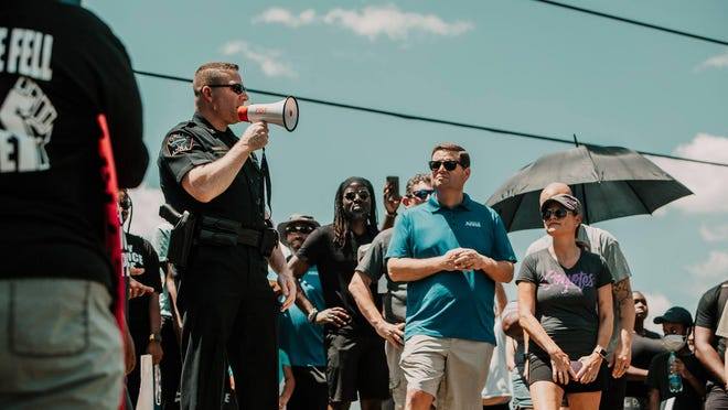 Anna Police Chief Jeff Caponera, left, addresses the crowd during a peaceful protest that took place in the city in June as Mayor Nate Pike and others look on. As part of a lighthearted online contest, Caponera has challenged residents to wear face masks and pose for photos with Anna Police officers.