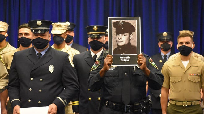 JPD officer holds a picture of Kenneth Tietjen, a first responder who lost his life on 9/11.