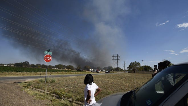 Citizens watch the smoke from a large house fire in Lubbock County on Thursday.